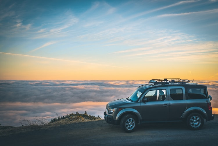 Car looking over clouds on road trip