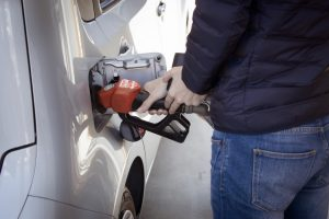 Person fills car tank with fuel